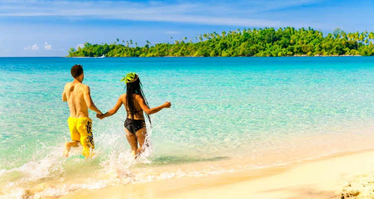 A loving couple, man and woman enjoying summer vacation on a tropical paradise beach with clear sea ocean water and scenic island on the horizon overgrown green palm on background blue summer sky