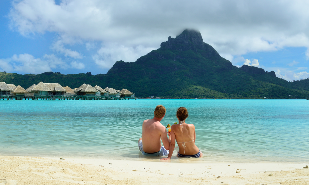 A honeymoon couple drinking a cocktail on the beach of a luxury vacation resort in the lagoon with a view on the tropical island of Bora Bora, near Tahiti,