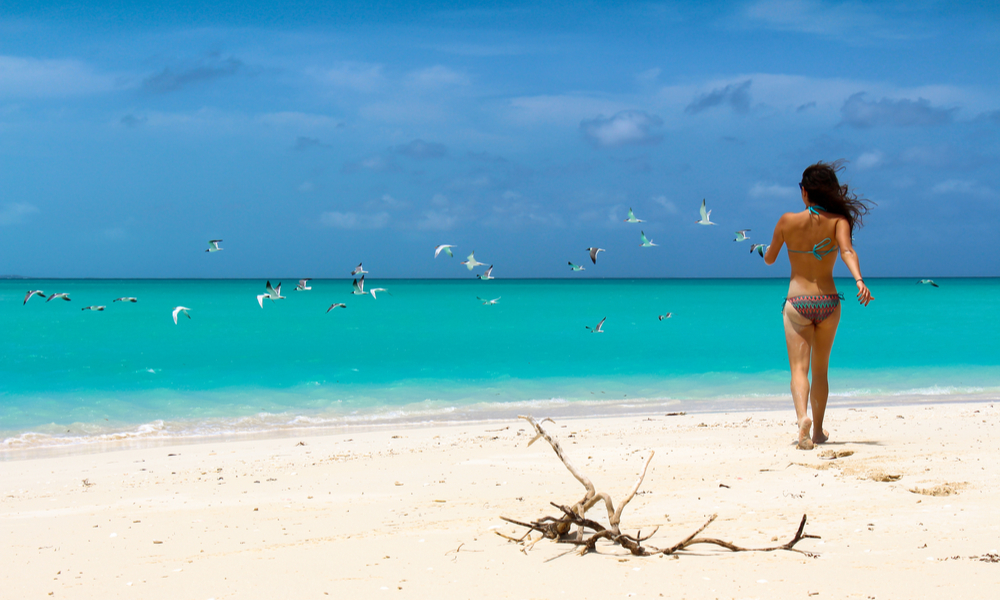 Attractive girl running on a white sanded beach on the islands of Turks and Caicos, Caribbean Sea