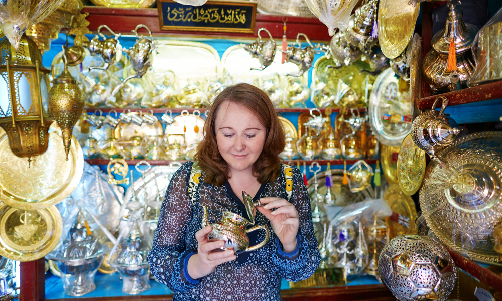 European tourist selecting a traditional teapot on Moroccan market