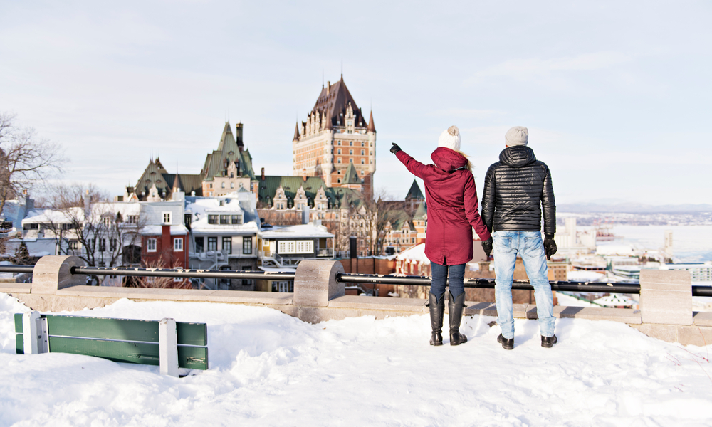 Young couple outside in winter with Quebec city Chateau frontenac