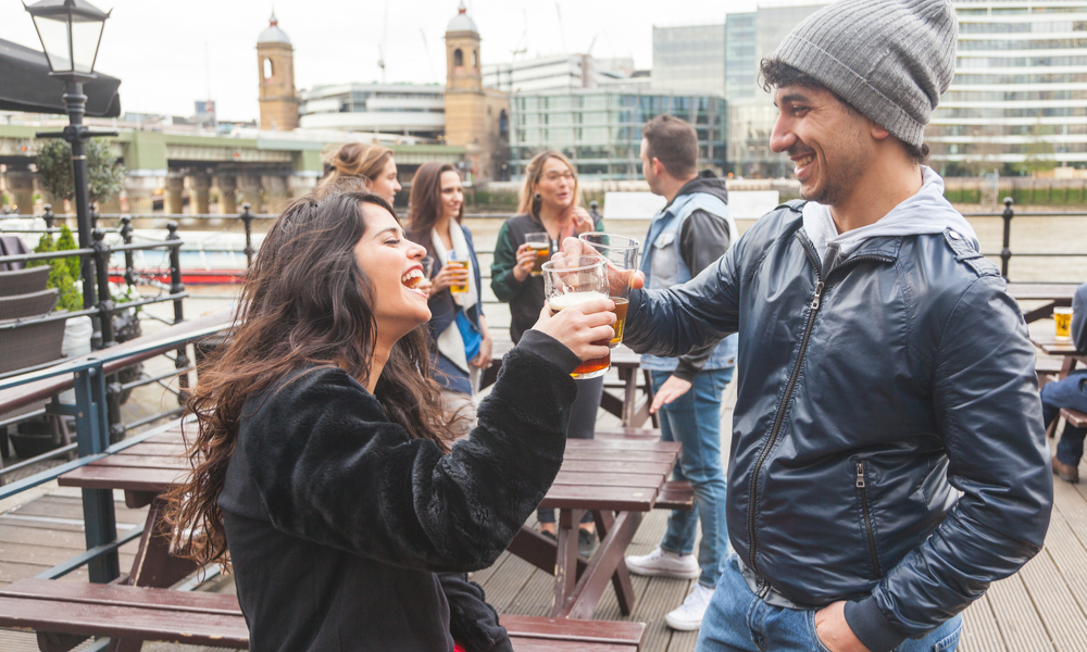 Young couple enjoying a beer at pub in London with more people on background.