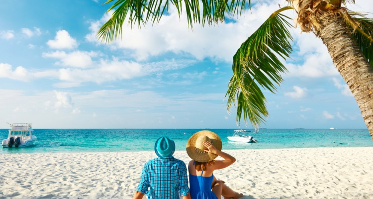 Couple in blue clothes on a tropical beach on a last-minute valentine's day getaway