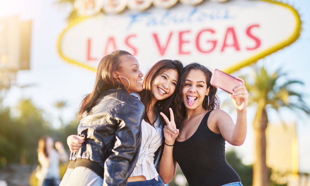 group of friends having fun taking selfies in front of welcome to las vegas sign