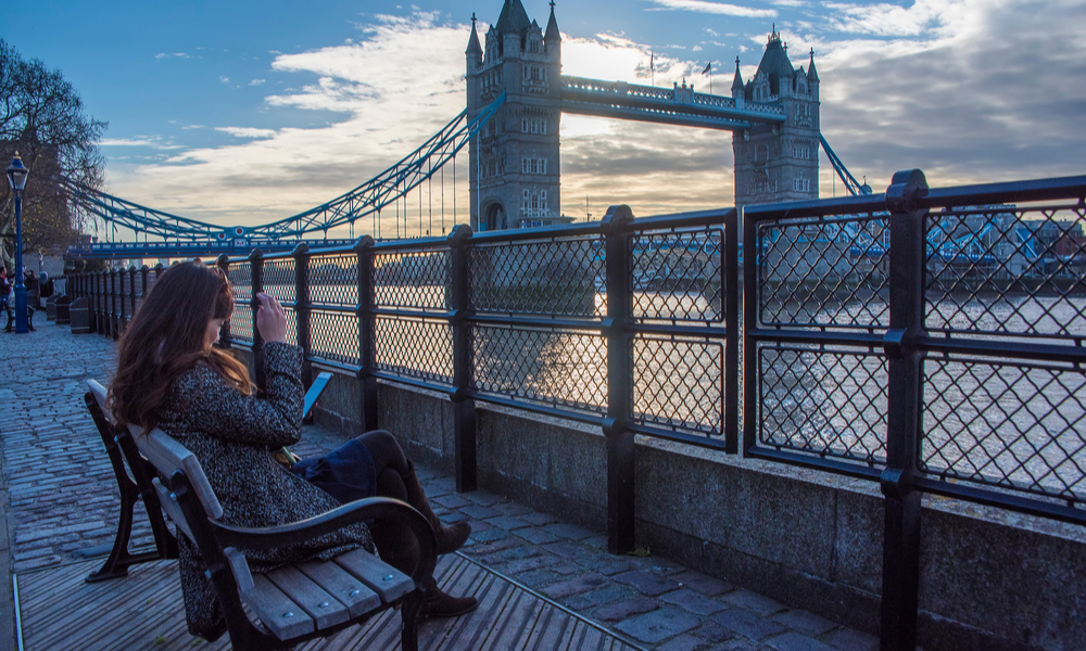 woman sitting on a bench overlooking the London Bridge