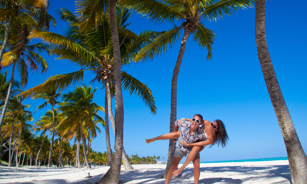 Happy young couple having beach fun piggybacking laughing together during summer holidays vacation on tropical Caribbean beach.