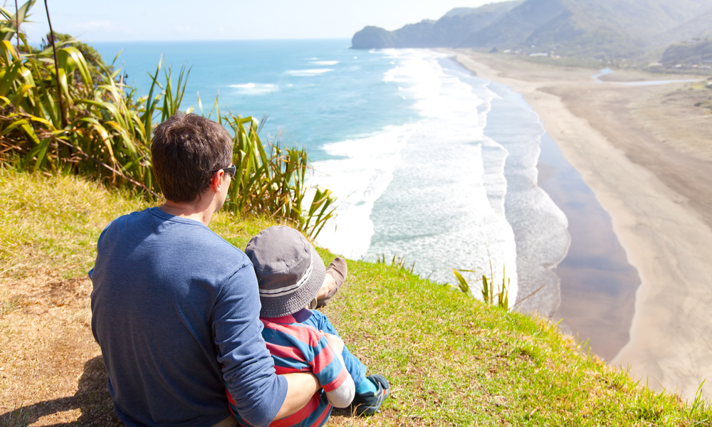 view of family sitting at the top of lion rock at piha beach, new zealand