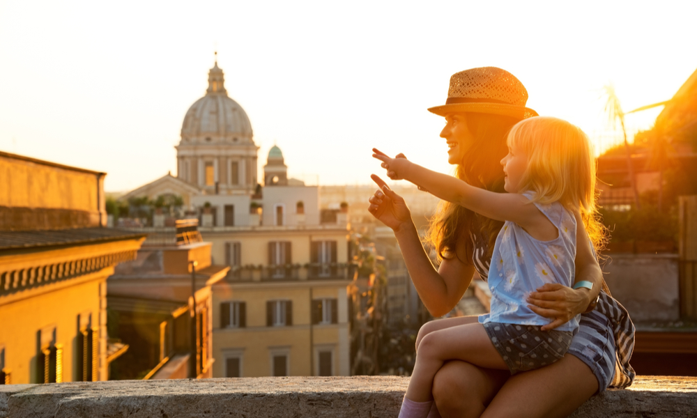 Mother and baby girl sitting on street overlooking rooftops of rome on sunset and pointing