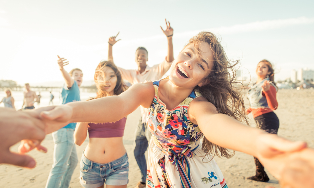 Group of friends having fun and dancing on the beach.