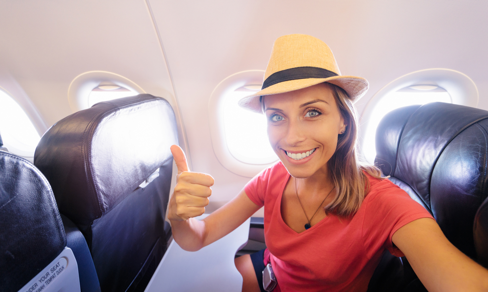 Young woman in plane taking selfie while sitting in airplane seat.