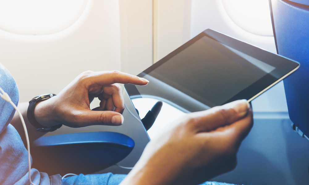 Side view of passenger using tablet in an airplane.