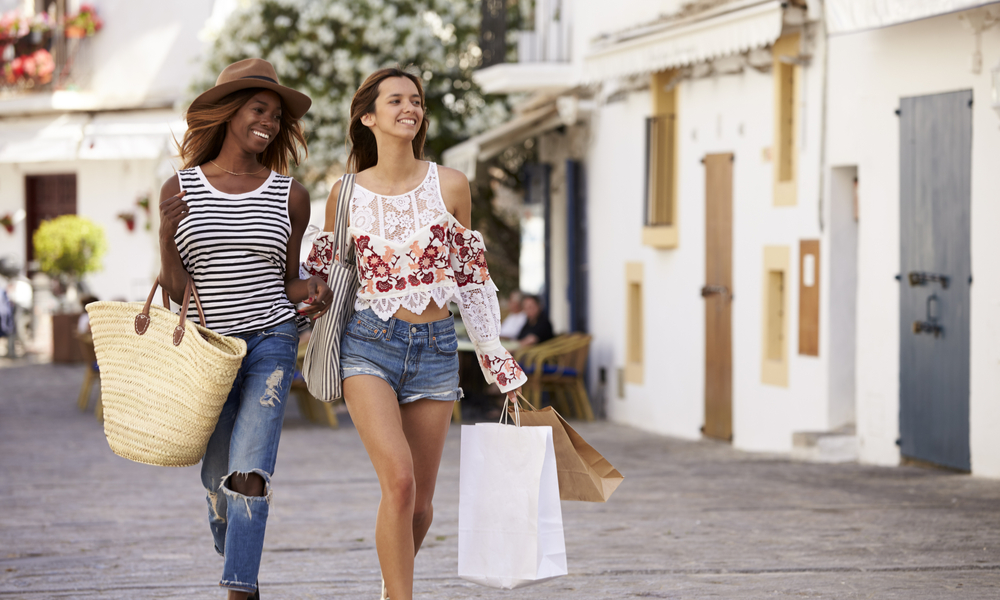 Two female friends on vacation shopping in Ibiza, front view