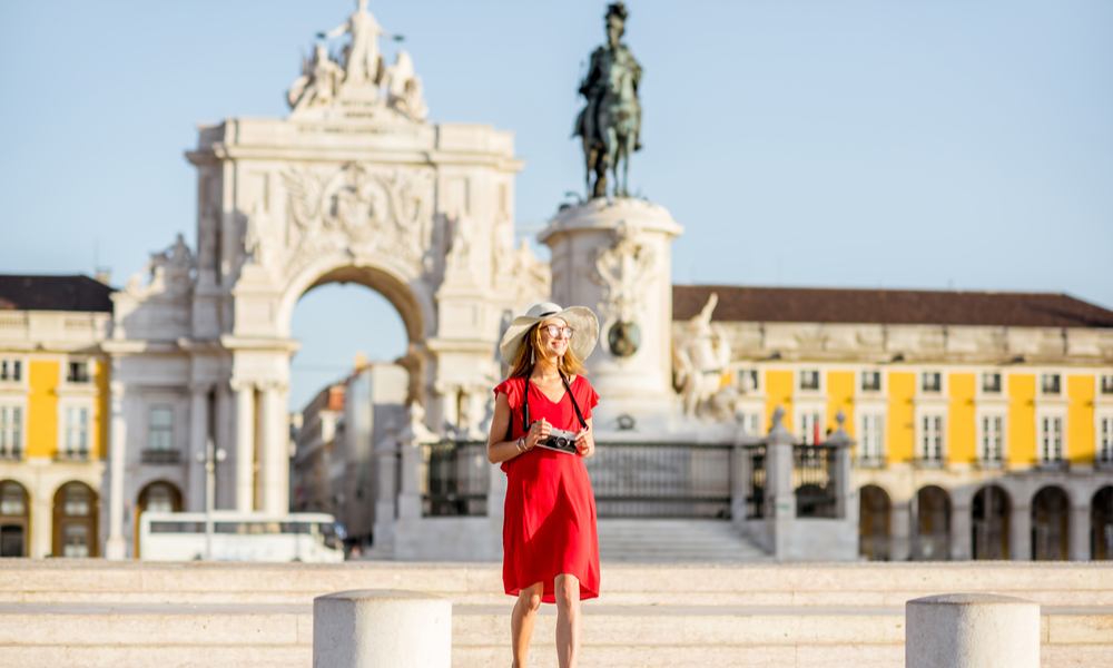 young woman tourist walking on the main square with statue and triumphal arch on the background during the morning light in Lisbon city, Portugal