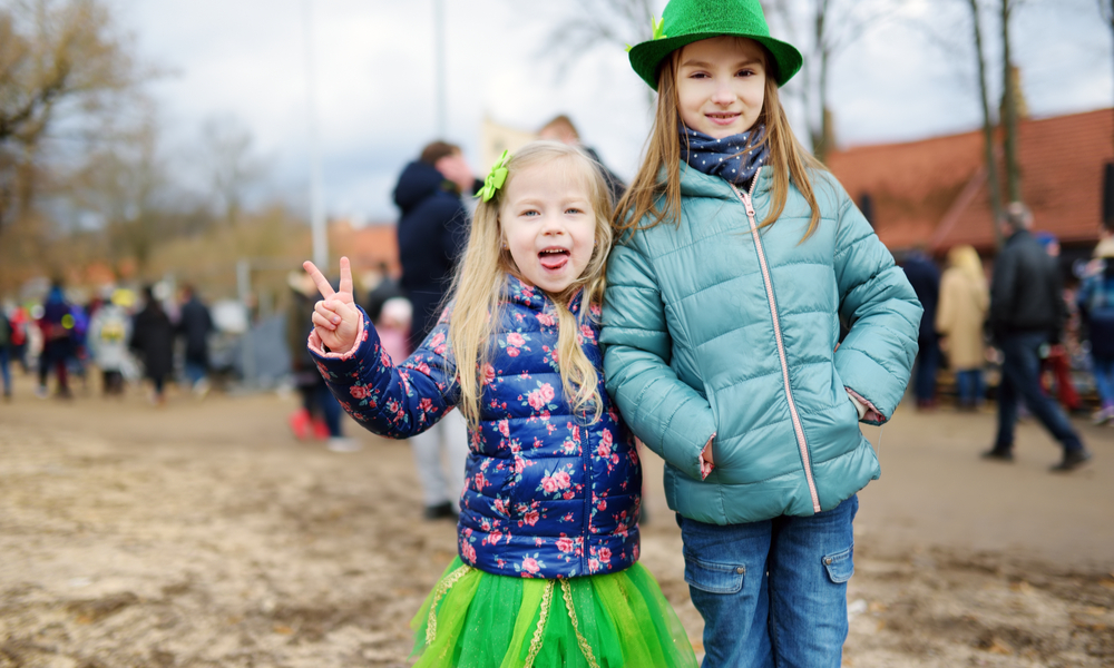 Two cute little girls wearing green hats and accessories celebrating St. Patrick's day