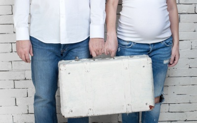 Pregnant woman with her husband standing against a white wall with a white suitcase