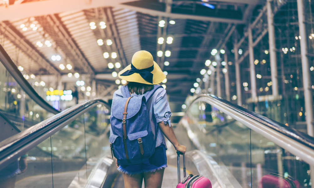 Young woman traveler in international airport with backpack holding suitcase or baggage in her hand