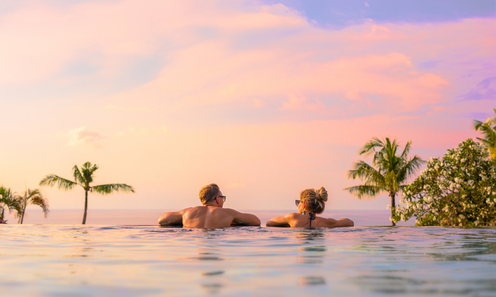 Romantic couple looking at beautiful sunset in luxury infinity pool in Bali