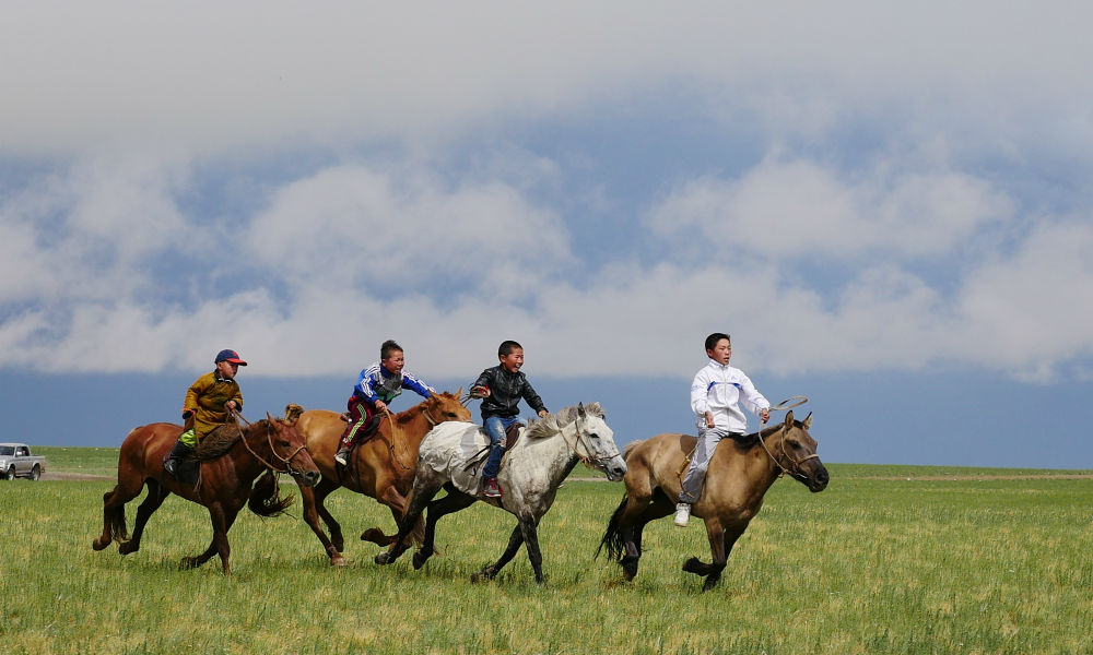 Mongolian children racing their horses