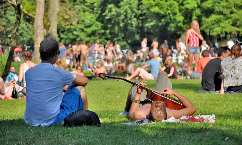 Two young men enjoy a summerday in the Vondelpark in Amsterdam. One of them is playing guitar, while the other one is looking at the people on the meadows in the background.