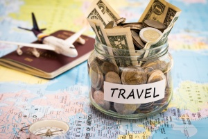 Travel money savings in a glass jar with compass, passport and aircraft toy on world map