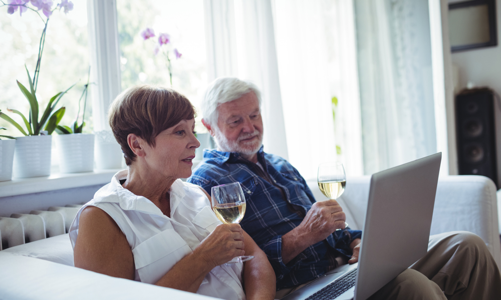 Senior couple sitting on sofa and using laptop in living room