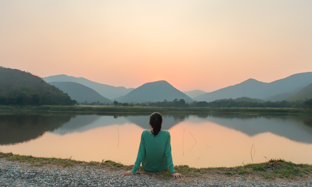 A woman is sitting at ease by the lake during sunset moment.