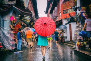 Rainy day girl tourist under red oriental umbrella in narrow alleys on china travel in Shanghai.