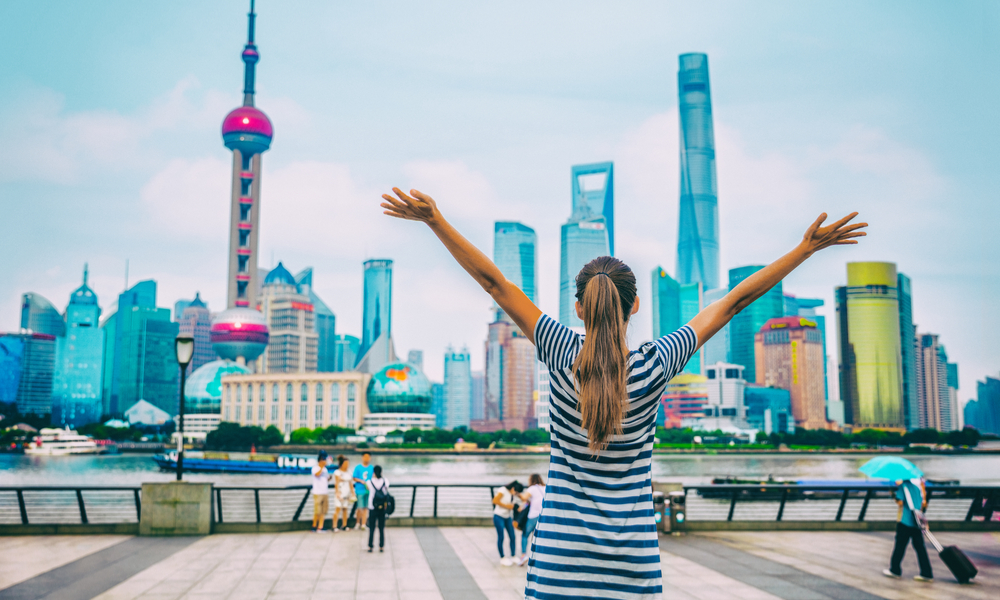 woman with arms up with Shanghai skyline on The Bund.