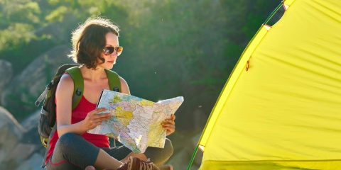 woman looking at a map near campsite