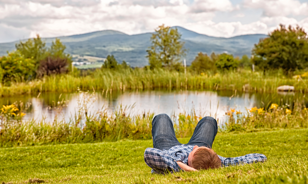 man relaxing near a river in Vermont