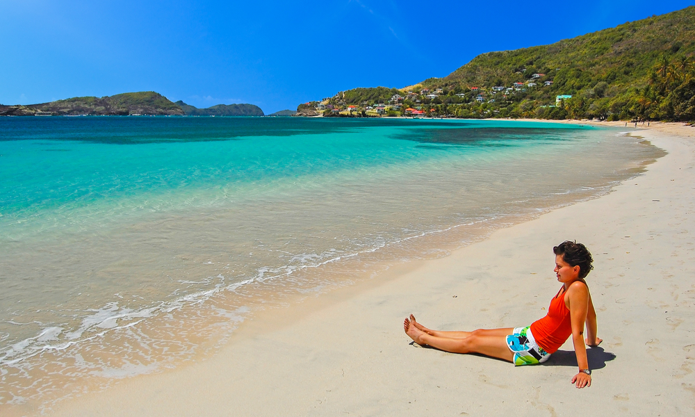 Young woman tourist sitting on tropical beach of Bequia Island, Caribbean Sea region of Lesser Antilles