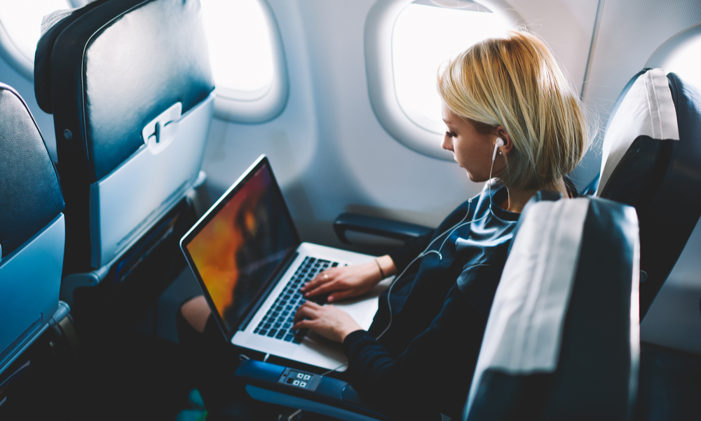 female passenger of airplane sitting in comfortable seat listening music in earphones while working at modern laptop computer with mock up area using wireless connection on board