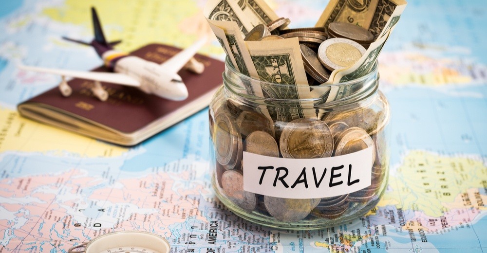 Travel budget concept. Travel money savings in a glass jar with compass, passport and aircraft toy on world map