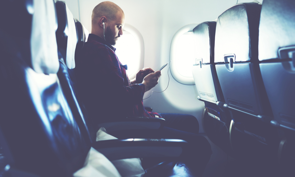 Man is listening to music in headphones and chatting in social network via mobile phone, during his flying in an airplane.