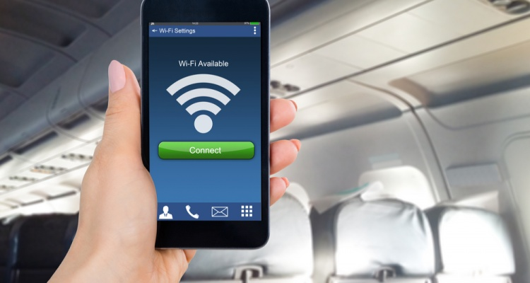 Close-up Of Person's Hand Holding Mobile Phone Showing WiFi Connection In Airplane
