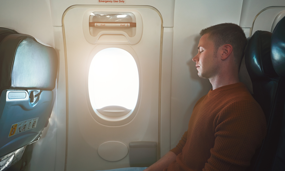 passenger sitting next to the exit door of a plane