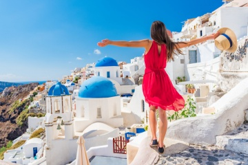 Europe travel vacation fun summer woman dancing in freedom with arms up happy in Oia, Santorini, Greece island.