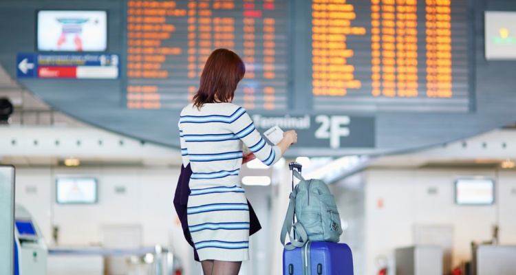 Young female passenger at the airport, looking at the flight information board