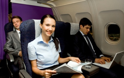 Image of pretty girl with magazine looking at camera while handsome man typing next to her