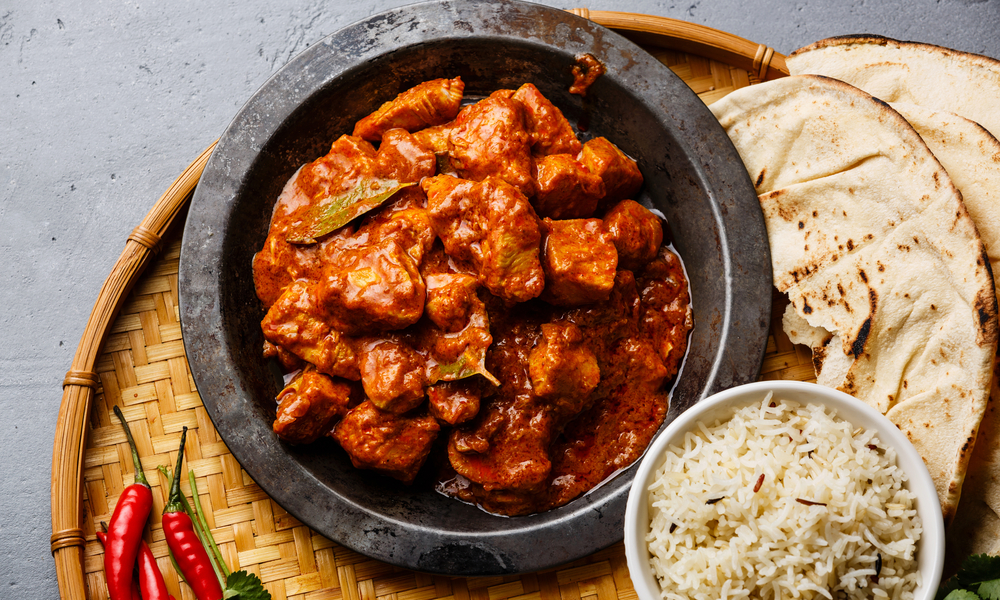 Chicken tikka masala spicy curry meat food in metal plate, rice and naan
