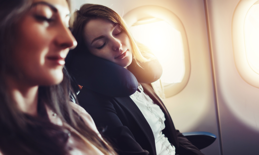 A female passenger sleeping on neck cushion in airplane.