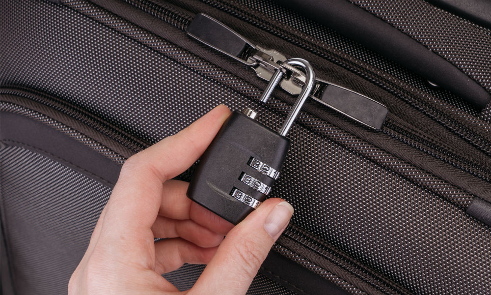 Hand opens suitcase combination lock on the gray suitcase.