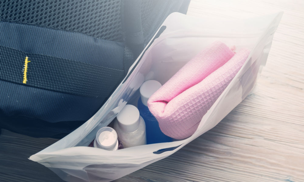 Set of travel bottles and towel in plastic bag