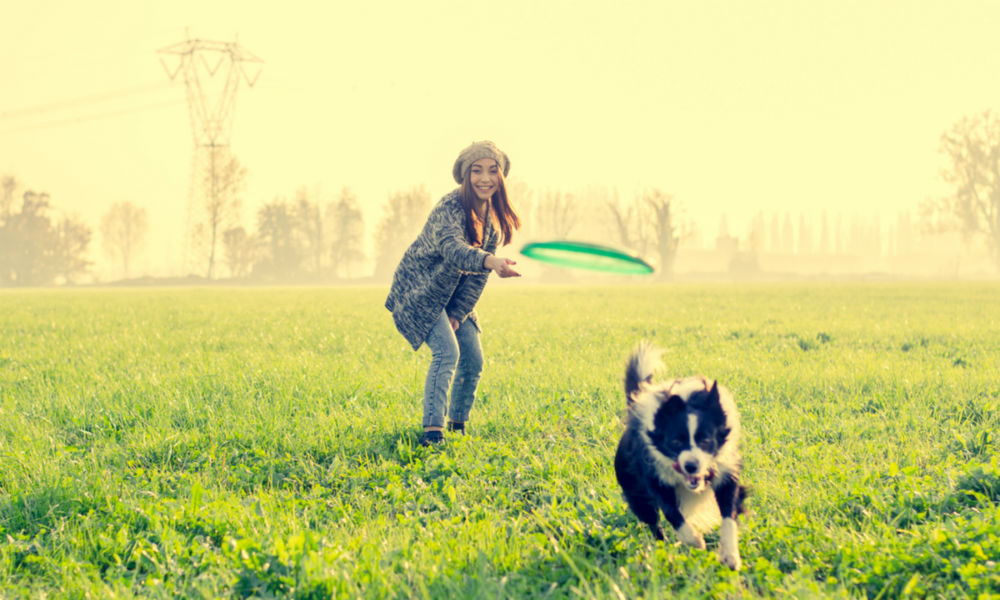 Asian woman playing with her dog