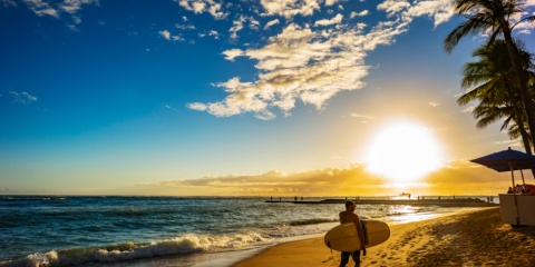 Surfer carrying board with sunset background