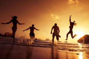 Group of happy young people is running on background of sunset beach and sea