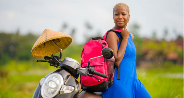 african american woman looking around with scooter motorbike at green field tropical landscape in adventure trip