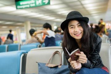 Asian woman solo traveler holding passport and waiting for flight travel at airport terminal