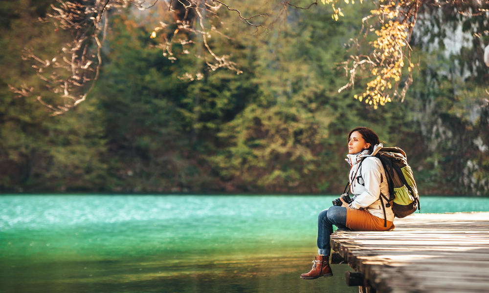 Woman traveler sits on wood bridge on mountain lake at sunny autumn day