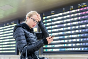 Stressed worried woman in international airport looking at smart phone app information and flight information board, checking her flight details.